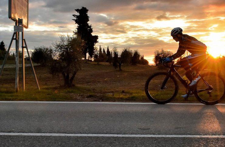 Ciclista che corre al tramonto. È Matteo Venzi, triatleta mentre si allena per la Ironman