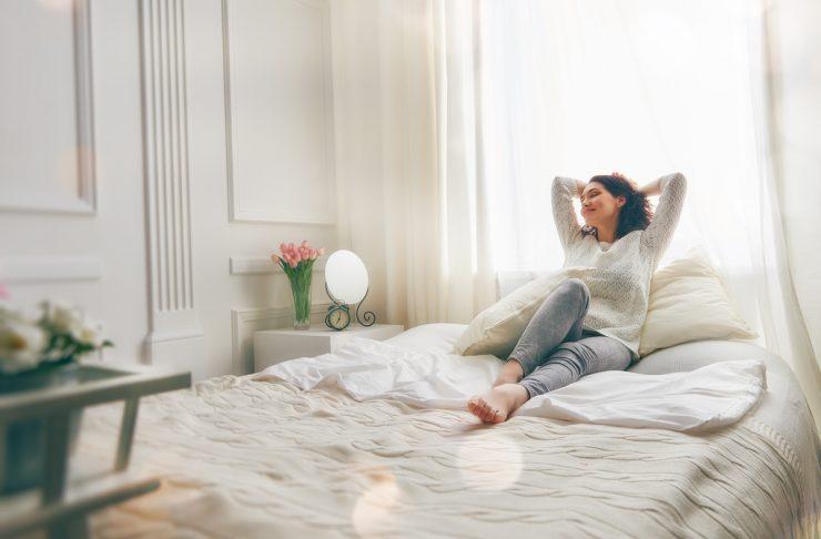 donna sul letto felice, scopri come dormire meglio in una camera da letto accogliente