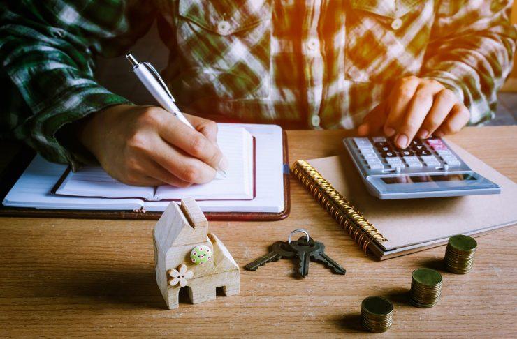 uomo con calcolatrice e fogli che fa i conti di casa, scopri come risparmiare in casa con i nostri cinque consigli indispensabili