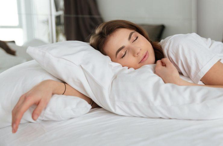 donna che dorme rilassata sul proprio letto. Scopri le quattro regole su come riuscire a dormire in poco tempo