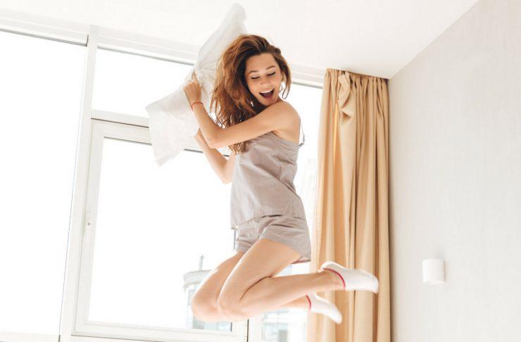 donna che salta sul letto, scopri come svegliarsi bene la mattina