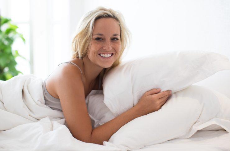 donna felice a letto perché riesce a dormire meglio, scopri come