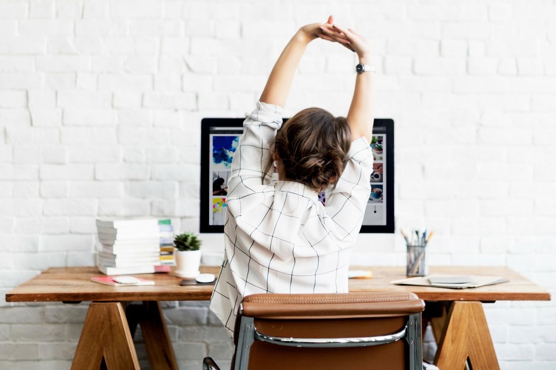 donna che stira le braccia ed esegue gli esercizi posturali per l'ufficio