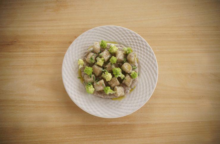gnocchi di farro e ceci serviti con crema di legumi