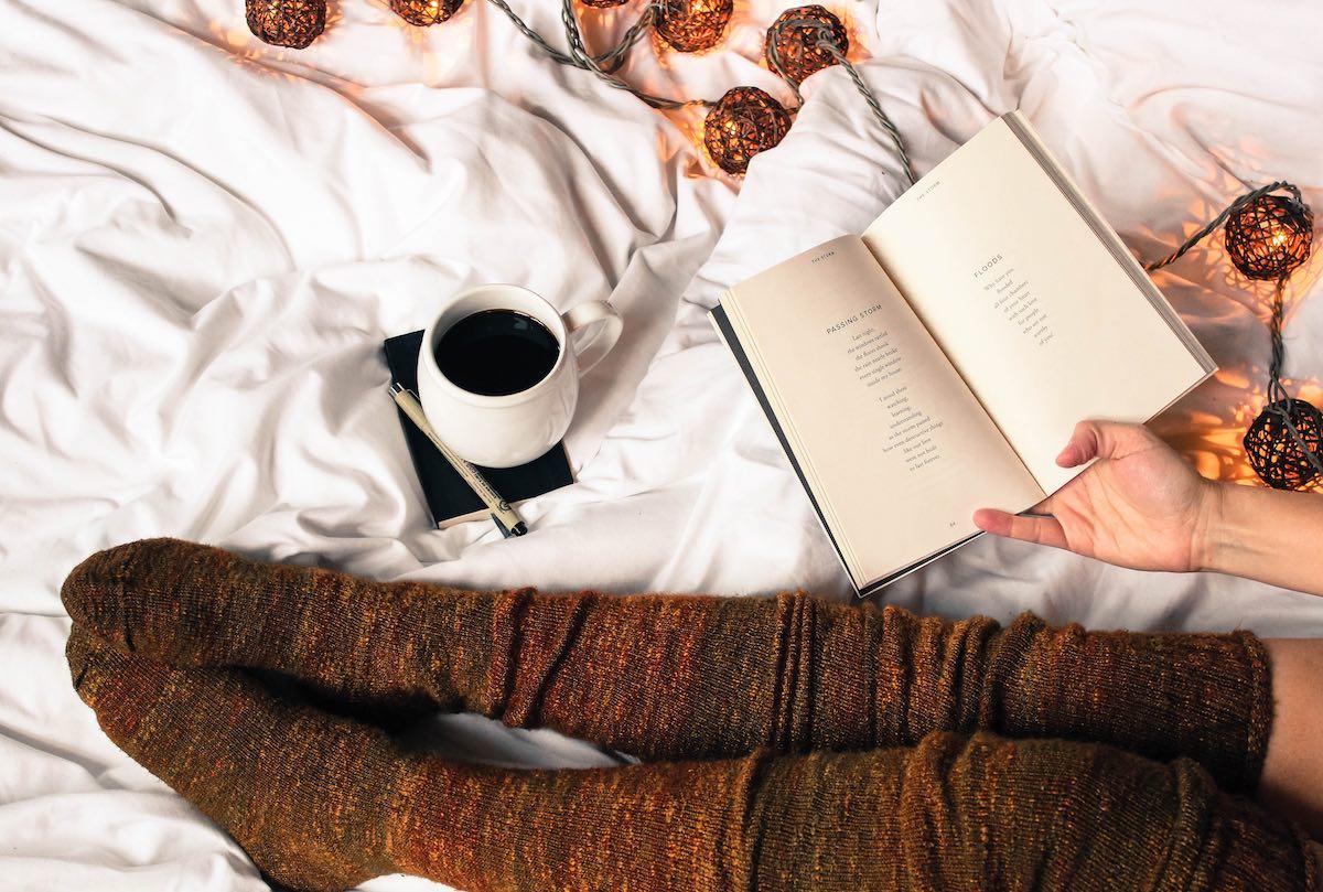 donna con calzettoni che legge un libro sul letto con luci soffuse in stile hygge