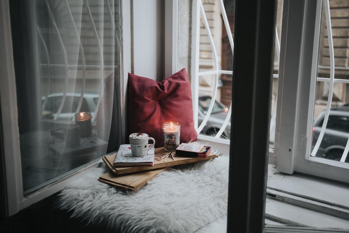 angolo di relax vicino alla finestra con coperte, cuscino e candele. In pieno stile hygge