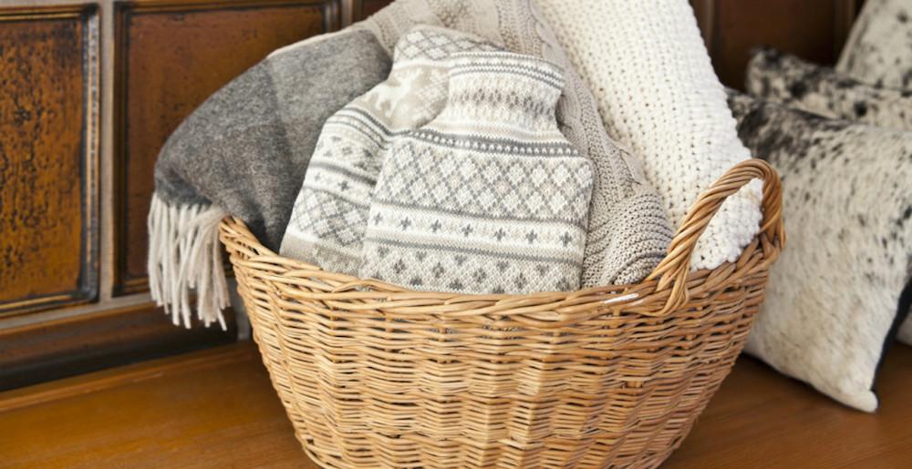 cesto di vimini con coperte di lana, una delle idee camera da letto di tendenza