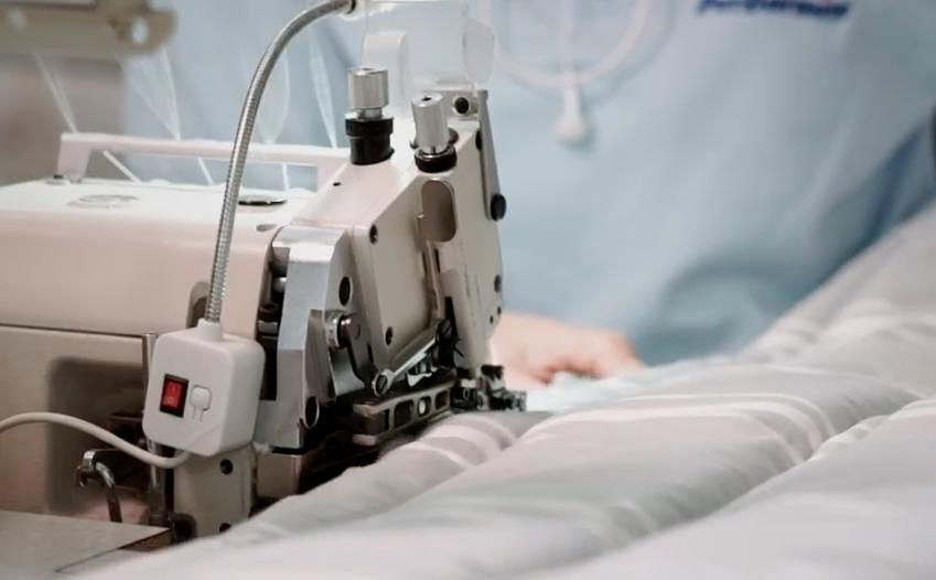macchina da cucire industriale e operaia mentre cuce il rivestimento di un materasso made in Italy prodotto da PerDormire