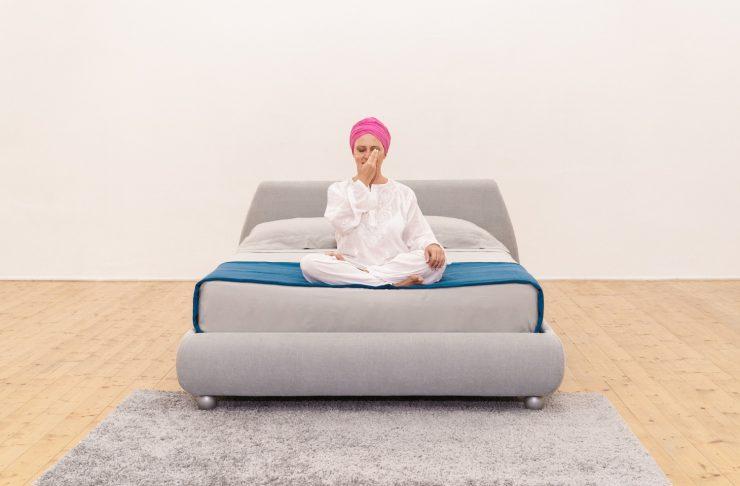 donna su letto che esegue una tecnica di meditazione per rilassarsi respirando alternando le narici