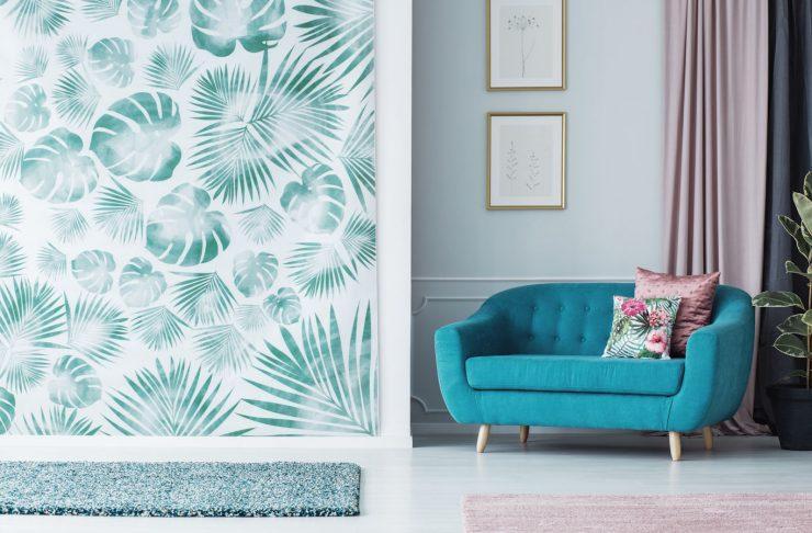 Una parete del soggiorno rivestita di carta da parati a stampa botanica