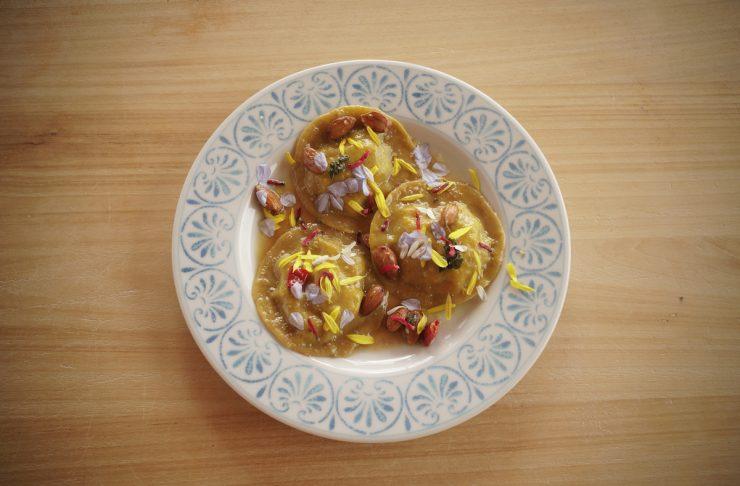 tortelli di zucca serviti con mandorle e fiori